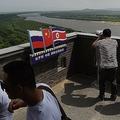 中国東北部の吉林省琿春で、展望台からロシア(左側)と北朝鮮(右側)の風景を眺める人々(2015年6月25日撮影、資料写真)。(c)AFP=時事/AFPBB News
