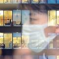 マスクを着けた男性が明かりがつくオフィスビルのガラスに写っている