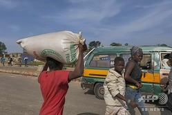 ナイジェリア中部ジョスで、襲撃した倉庫から食料の袋を持ち去る女性(2020年10月24日撮影)。(c)Ifiok Ettang / AFP
