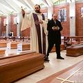 イタリア北部ロンバルディア州ベルガモ近郊の教会に並べられたひつぎに祝福を与える神父(2020年3月28日撮影)。(c)Piero CRUCIATTI / AFP