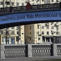 モスクワ中心部で「家にいて。あなたのモスクワ交通局」と書かれた橋の前で写真撮影をする人(2020年3月29日撮影)。(c)Alexander NEMENOV / AFP