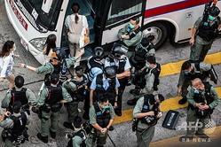 香港で行われた国家安全法に対する抗議デモで拘束され、警察のバスに乗せられる参加者ら(2020年6月28日撮影)。(c)ISAAC LAWRENCE / AFP