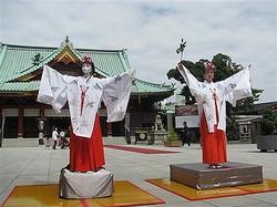 神田明神の御神殿の前で巫女舞を奉納するロボット「高坂ここな」(左)と、大畑杏雛さん=14日、東京都千代田区