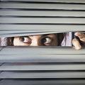 閉じたブラインドの隙間からあたりを覗く緊張した女性