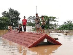 ダムの決壊で村が水没、家の屋上に避難した住民たち。(写真/時事通信社)