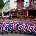 仏パリの老舗キャバレー「ムーランルージュ」の前で、営業再開日を告知するダンサーら(2021年5月17日撮影)。(c)MARTIN BUREAU / AFP