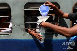 インドで、列車の乗客に飲み水を売る行商人(2014年5月7日撮影、資料写真)。(c)Chandan KHANNA / AFP