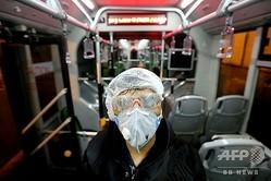 イラン・テヘランで、新型コロナウイルスの感染拡大阻止のためバス内を清掃する市職員(2020年2月26日撮影)。(c)ATTA KENARE / AFP