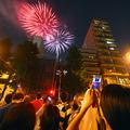 2015年の隅田川花火大会で、ビルの間から花火を見上げる人たち(写真=時事通信フォト)