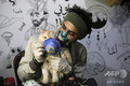 パレスチナ自治区のガザ市で、新型コロナウイルスについての意識向上を目指したプロジェクトのため、猫の顔の前でマスクを持つアーティスト(2020年3月24日撮影、資料写真)。(c)MOHAMMED ABED / AFP