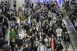香港の地下鉄駅を歩くマスク姿の通勤客ら(2020年11月25日撮影)。(c)Anthony WALLACE / AFP