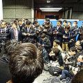 報道陣に囲まれながら、事業継続の意思はあると強調した大塚COO(左端)