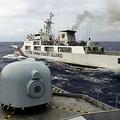ナトゥナ諸島周辺の海域で、インドネシア海軍の軍艦(手前)の前を横切る中国海警局の船=2020年1月11日、アンタラ通信
