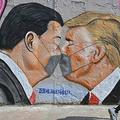 米国のドナルド・トランプ大統領(右)と中国の習近平国家主席を描いた、グラフィティアーティストのエメ・フリーシンカー氏の壁画(2020年4月28日撮影、資料写真)。(c)Photo by John MACDOUGALL / AFP