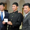 ヤクルトの伊東昭光編成部長(右)と阿部健太担当スカウト(左)から指名のあいさつを受ける奥川恭伸