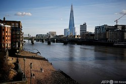 新型コロナウイルス対策のロックダウン(都市封鎖)が実施されている英首都ロンドン中心部で、テムズ川のそばを歩く人々(2021年1月22日撮影)。(c)Tolga Akmen / AFP