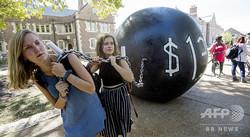 米ミズーリ州セントルイスのワシントン大学セントルイス校で、学費ローンの重さを皮肉って表現してみせる学生たち(2016年10月9日撮影)。(c)PAUL J. RICHARDS / AFP