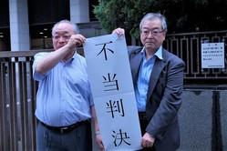住民が起こした控訴審の判決は敗訴。「不当判決」の旗を出すのは、原告の高橋新一さん(左)と宮坂健司さん