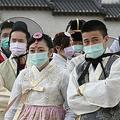 韓国・ソウルの景福宮で、伝統衣装とマスクを着用した観光客ら(2020年1月30日撮影)。(c)Jung Yeon-je / AFP