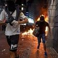 香港で燃える地下鉄の駅の入り口から走り去る抗議デモの参加者(2019年10月4日撮影、資料写真)。(c)Mohd RASFAN / AFP