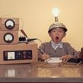 頭に電球が光っている発明家のような子どもと機械の模型