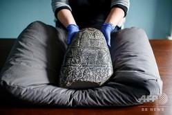 イラクから盗まれた古代バビロニアの石板を手にする博物館職員。英ロンドンの大英博物館にて(2019年3月19日撮影)。(c)Tolga Akmen / AFP
