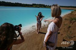 シベリア・ノボシビルスクの発電会社の灰処分地の湖でカメラに向かってポーズをとる女性(2019年7月11日撮影)。(c) Rostislav NETISOV / AFP