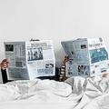 アジアのカップルがベッドで新聞を読む