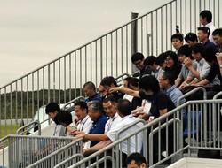 五輪カヌー会場の観客席で、横付けした降雪機を使って暑さ対策の実験を行った。前列右から2人目は室伏広治氏
