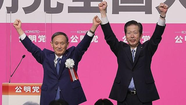 公明党の党大会で、壇上で山口那津男代表(右)と両手を上げる来賓として出席した菅義偉首相=2020年9月27日日、東京都千代田区