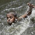 インド・ニューデリーの池で涼を取る少年(2020年5月26日撮影)。(c)Money SHARMA / AFP