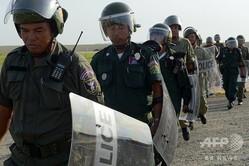 カンボジアの首都プノンペンで、訓練中に一列に並んで歩く警官ら(2013年9月1日撮影、資料写真)。(c)TANG CHHIN SOTHY / AFP