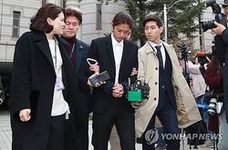 令状審査を終え、ソウル中央地裁から出て来たチョン容疑者=21日、ソウル(聯合ニュース)