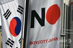 韓国のソウル特別市中区に掲げられた韓国の国旗(左)と、日本製品のボイコットを呼びかける旗(2019年8月6日撮影、資料写真)。(c)Jung Yeon-je / AFP