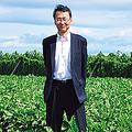 利用者でもある農家の池守明裕さんの農地に立つ瀬下さん。池守さんは「そのデータに基づいて与える肥料の調整を行うことで、小麦の生育を均一にできます。その結果、出荷時の品質を保て、収入増につながり大変助かります」と太鼓判を押す。