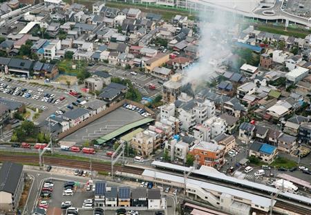 白煙を上げて燃える京都アニメーションのスタジオ。手前は京阪六地蔵駅=18日午後0時13分、京都市伏見区(本社ヘリから、鳥越瑞絵撮影)