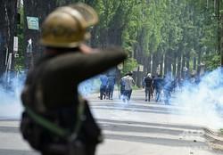 インド北部ジャム・カシミール州の主要都市スリナガル郊外で、抗議デモに向かって催涙弾を発射する警察官(2019年5月13日撮影)。(c)AFP=時事/AFPBB News