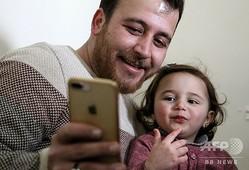 シリア・イドリブ県サルマダの自宅で、スマートフォンの画面をのぞくアブドラ・ムハンマドさんと娘のサルワちゃん(2020年2月19日撮影)。(c)Abdulaziz KETAZ / AFP