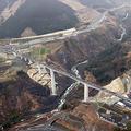 国道325号阿蘇大橋ルートが開通し、新阿蘇大橋(中央)を通り初めする車両。右奥の上流部分は、熊本地震で旧阿蘇大橋が崩落した現場=2021年3月7日午後0時20分、熊本県南阿蘇村、朝日新聞社ヘリから、堀英治撮影