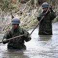 雨が降る中、まだ濁った水が流れる川に入り行方不明者の捜索を行う自衛隊員(14日午後2時57分、福島県郡山市で)=上甲鉄撮影