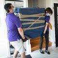 カナダ・ケベック州ラバルで、引っ越し業者に指示を出すデザイナーのシェイラ・ダッサンさん(右、2020年7月1日撮影)。(c)Sebastien St-Jean / AFP
