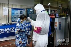 中国・武漢の地下鉄駅の入り口で、乗客の体温を測る当局者(2020年1月28日撮影)。(c)NOEL CELIS / AFP