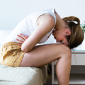 Shot of unhealthy young woman with stomachache leaning on the bed at home.
