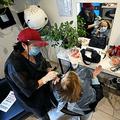 美容院で、マスクとフェースシールドを着けて接客する美容師。イタリア・ローマにて(2020年5月18日撮影)。(c)Alberto PIZZOLI / AFP