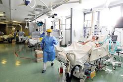 イタリア北部ベルガモの病院の集中治療室で5月12日、新型コロナウイルス患者の治療に当たる医療従事者(中央)=ロイター