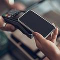 クレジットカード決済機にスマートフォンを置く若い女性の手