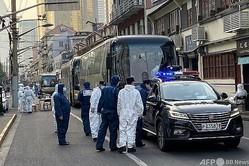 中国・上海の黄浦区の隔離対象となった住宅街で、バスのそばに立つ防護服姿の警察官ら(2021年1月21日撮影)。(c)STF / AFP