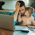 キッチンで頭を抱える父親と、その膝の上でくつろぐ娘