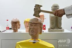 中国・上海で開催中の家電見本市「CESアジア」に日本のIT企業ソリトンシステムズが出展した「ストレス解消」ブースで、ドナルド・トランプ米大統領の頭部の模型をたたく来場者(2019年6月11日撮影)。(c)HECTOR RETAMAL / AFP