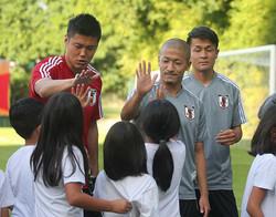 日本代表練習を見学に訪れた生徒らとタッチする川島(左)と前田(撮影・大塚 徹)